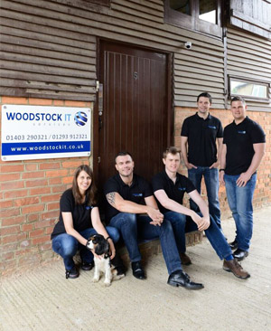 the woodstook team infront of sign
